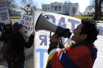 A protester opposed to the Chinese government policies towards Tibet shouts through a bullhorn on the sidewalk outside the White House in Washington