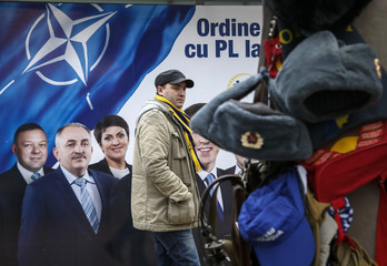 A man passes by as a street vendor sells Soviet Union military uniforms in front of a pre-election poster for the Liberal Party in Chisinau