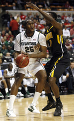 Michigan State University center Nix looks to shoot on University of Iowa center Olaseni during the second half of play in the second round of the Big Ten men's basketball tournament in Indianapolis