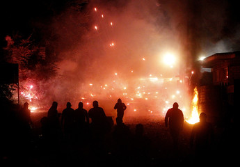 Protesters throw firecrackers during violent overnight protests against the opening of a new waste dump in Terzigno, outside Naples