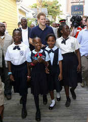 Britain's Prince Harry walks with children during a tour of Harbour Island in Nassau