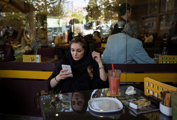 Iranian woman uses her mobile phone to follow election news in a coffee shop in Tehran