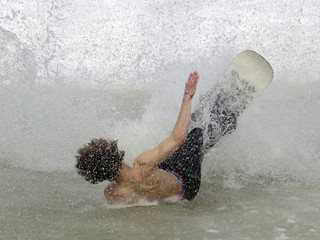 A snowboarder crashes in a 20 meter long pool of water during a water slide event on the Tracouet Lake in Nendaz