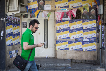 Man uses his smartphone to follow election news in Tehran