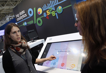 An exhibitor explains the usage of big data analytics at the booth of IBM during preparations for the CeBIT trade fair in Hanover