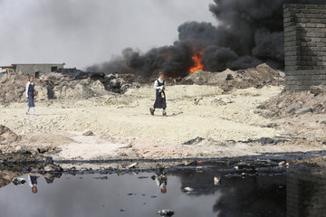 Girls walk as smoke rises from oil wells, set ablaze by Islamic State militants before IS militants fled the oil-producing region of Qayyara