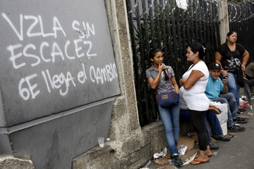 """People line up next to graffiti that reads, """"Venezuela without shortages, 6E the change arrives"""", while they try to buy cooking oil and milk, outside a supermarket in Caracas"""