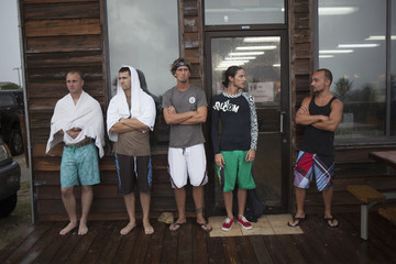 Surfers Robert Drew, Brad Thomas, Tim Duncan, Pate Futch, and Benjamin Hewett, wait for good waves outside an arcade during Hurricane Arthur, in Ocean Isle Beach