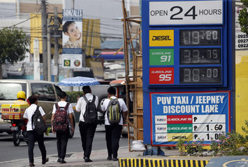 Students walk on a sidewalk past different oil prices posted at  Unioil petrol station beside a highway in Paranaque city, Metro Manila