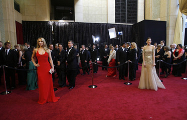 Actresses Jennifer Lawrence and Mandy Moore pose for photographers on the red carpet at the 83rd Academy Awards in Hollywood