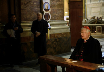 Cardinal Angelo Scola of Italy prays before giving mass at the Santi XII Apostoli in Rome
