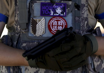 "A participant of a ""survival game"" shows his air gun under his favorite animation character patch (top) which also reads, ""package direct from battlefield"" at a field in Chiba, Japan"