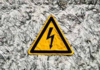 Warnschild für Strom auf Faserhintergrund