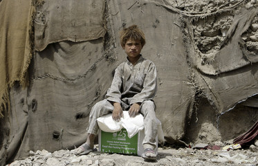 An Afghan internally displaced boy receives charity from the Islamic Relief organisation in Kabul