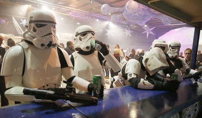People dressed as Storm troopers stand at a bar as they pose for a photograph holding cans of beer at the  'For The Love of The Force' Star Wars fan convention in Manchester , northern England