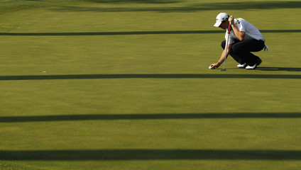 Rory McIlroy of Northern Ireland places his ball on the 10th green during third round play in the 2011 Masters golf tournament in Augusta