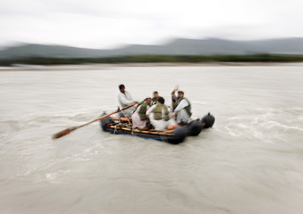 Local residents use a rudimentary ferry service to cross the Swat River at Kanju in Pakistan's Swat Valley