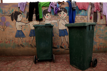 Clothes of newly displaced people are seen hanging to dry on a wall at the school at Debaga Camp on the outskirts of Erbil
