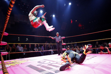 Lucha libre wrestler Dr. Maldad leaps in midair while fighting against a member of The Crazy Chickens during the Lucha VaVOOM show at the Mayan Theatre in Los Angeles