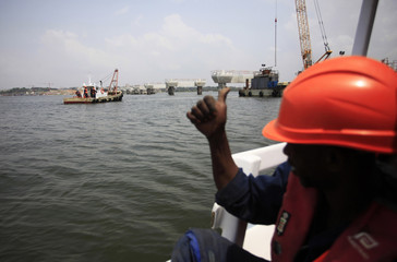 A worker gives the thumbs-up to his colleagues as they go about constructing Ivory Coast's third bridge, the Henri Konan Bedie in Abidjan