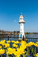 Yellow Tulips blooming in front of the Robert Scott Memorial Lighthouse at Roath Park Lake, Cardiff, Wales, UK.