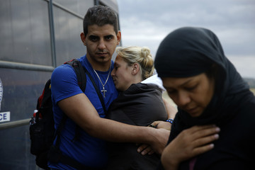 Syrian refugees stand by police bus near the Greek-Macedonian border