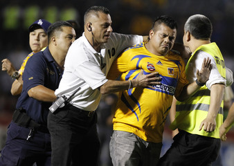 Security officers detain a Tigres' fan that invaded the pitch at the end of their Mexican league championship soccer match against Toluca in Monterrey