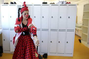 Kaltenrieder also known as clown doctor Schmatz of the Theodora foundation puts on her red clown nose in a cloak room at the Insel university's hospital for children in Bern