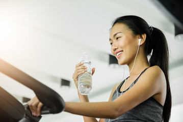 Asian woman in sportswear drinking water after workout at the gym.