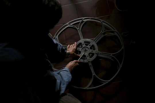 Projectionist Antonio Feliciano prepares a reel before a projection in Monforte