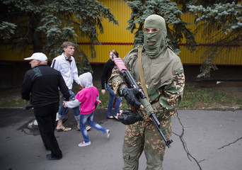 People walk past an armed pro-Russian separatist at a town center in Snizhnye in eastern Ukraine