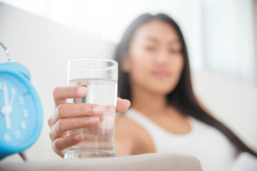 Close up Asian Woman holding glass of water with alarm clock.