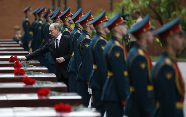 Russia's President Putin lays flowers during a ceremony to commemorate the anniversary of the beginning of the Great Patriotic War against Nazi Germany in 1941 near memorials by the Kremlin walls in Moscow