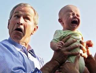 File photo of US President Bush handing back a crying baby that was handed to him in Trinwillershagen