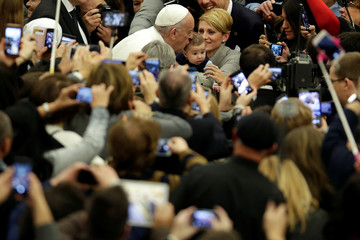 Pope Francis kisses a baby as he leads the weekly audience in Paul VI hall at the Vatican