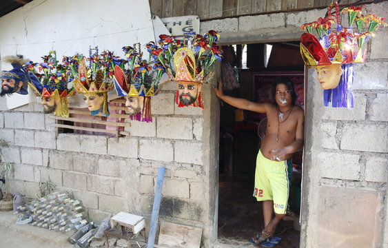 """Penitent Jhun Mazon smokes a cigarette at the entrance of his house next to """"Morions"""" masks used by members of his family during Holy Week celebrations in Mogpog, Marinduque in central Philippines"""