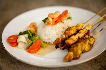 Indonesian Sate Satay Ayam -  grilled Spicy chicken skewers in spicy chili peanut sauce with steamed vegetables and rice.