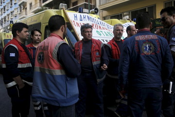 Rescuers of the Greek National Centre of First Aid stand next to ambulances during a protest outside the Health Ministry against government policies affecting their sector in Athens