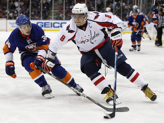 Washington Capitals Alex Ovechkin skates with the puck past the defense of the New York Islanders Travis Hamonic during the third period of their NHL hockey game in Uniondale