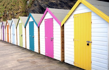Row of colourful multi colored beach huts at a seaside location