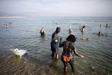 A couple makes their way to the Dead Sea, near the West Bank Jewish settlement of Mitzpe Shalem