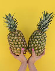 Girl's hand holding two pineapples on yellow background