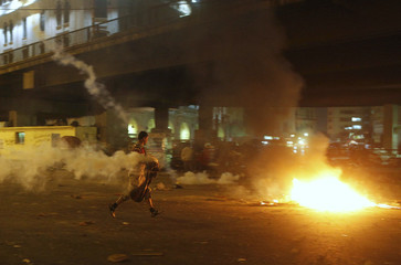 A supporter of deposed president Mursi runs to dispose a tear gas fired by police during clashesin Cairo