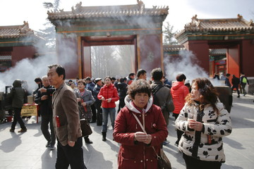 Jiang Huijun, whose family member was onboard Malaysia Airlines flight MH370 which went missing in 2014, burns incense sticks and prays with other relatives of passengers at Lama Temple in Beijing