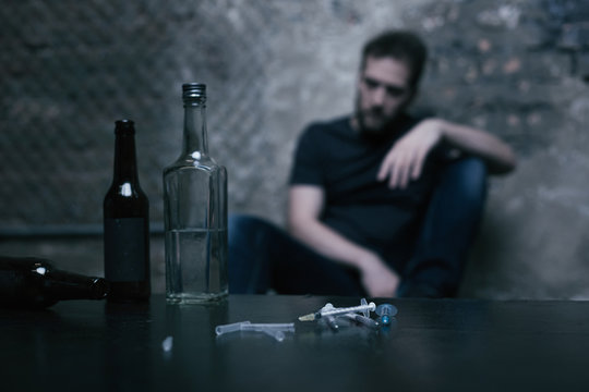 Alcohol in bottles and used syringes lying on the table