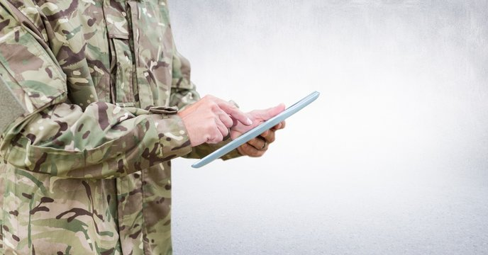 Soldier mid section with tablet against white wall