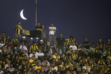 Fans of Uruguay's Penarol watch the Copa Libertadores soccer match against Ecuador's LDUQ as the crescent moon is seen in the background, in Montevideo