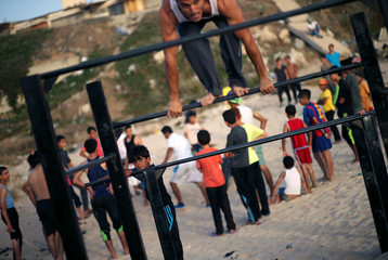 A Palestinian boy watches a member of Bar Palestine team as he demonstrates his street workout skills during a training session on a beach in Gaza City