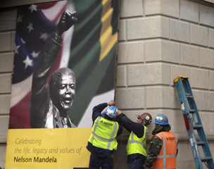 Construction workers erect a sign in honor of Nelson Mandela outside of the South African Embassy in Washington