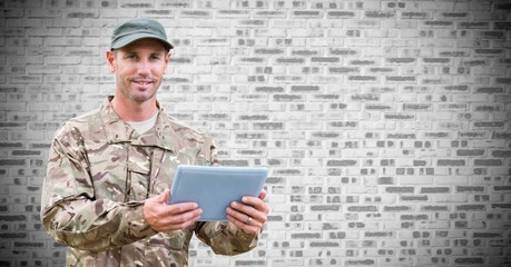 Soldier with tablet against white brick wall